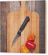 Peppers And Knife On Cutting Board Wood Print