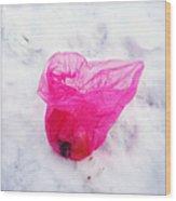Pink plastic bag lying on white snow Wood Print