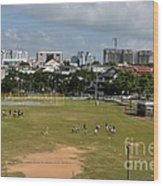Schoolchildren Practicing On Playing Field With Singapore Skyline In Background Wood Print