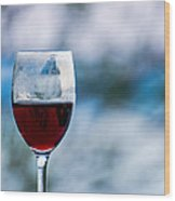 Single Glass Of Red Wine On Blue And White Background Wood Print