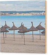 Straw Umbrellas On Empty Beach Wood Print