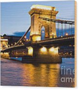 The Chain Bridge In Budapest Lit By The Street Lights Wood Print