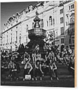 tourists and visitors sit on the steps of the eros statue in picadilly circus London England UK Wood Print