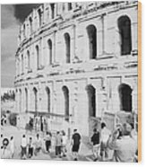 Tourists Walk Down Steps Towards  The Main Entrance Of The Old Roman Colloseum Against Blue Cloudy Sky El Jem Tunisia Wood Print