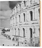 Tourists Walk Down Steps Towards  The Main Entrance Of The Old Roman Colloseum Against Blue Cloudy Sky El Jem Tunisia Vertical Wood Print