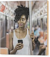 USA, New York City, Manhattan, portrait of relaxed woman with cell phone in underground train Wood Print