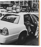 white caucasian passenger closes rear door of yellow cab on taxi rank at crosswalk on 7th Avenue Wood Print