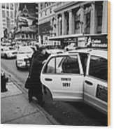 white middle aged passengers exit from yellow cab rear door at taxi rank on 7th Avenue Wood Print