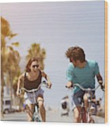 Woman chasing man while riding bicycle Wood Print