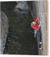 Woman Climbing Above A River Wood Print