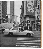 yellow cab taxi blurs past pedestrian waiting at crosswalk on Broadway outside macys new york usa Wood Print