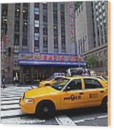 Yellow Cabs Pass In Front Of Radio City Music Hall Wood Print