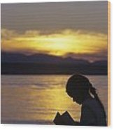 Young Girl Silhouetted Reading A Book On The Beach At Sunset Wood Print