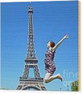 Young Woman Jumping Against Eiffel Tower Wood Print
