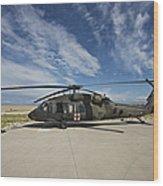 A Uh-60l Blackhawk Parked On Its Pad Wood Print