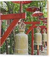 Row Of Bells In A Temple Covered By Red Umbrella Wood Print