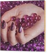 Woman Hand With Purple Nail Polish On Candy Wood Print