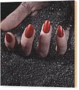 Woman Hand With Red Nails On Black Sand Wood Print