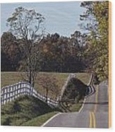 A Hilly Country Road Passes A Fenced Wood Print