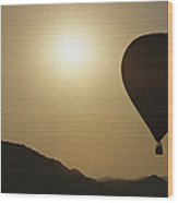 A Hot Air Balloon Rises Above A Hilly Wood Print