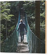 A Man Walks Across A Suspension Bridge Wood Print by Taylor S. Kennedy