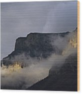 A Mountain Peaks Through The Clouds Wood Print