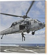 A Naval Aircrewman Is Hoisted Into An Wood Print