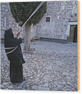 A Nun Pulls On Ropes In A Courtyard Wood Print by Tino Soriano