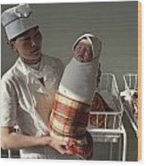 A Nurse Holds A Tightly Wrapped Newborn Wood Print by Dean Conger