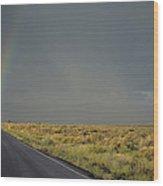 A Rainbow Touches A Rain Soaked Road Wood Print