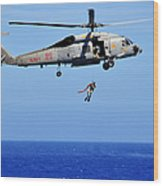 A Search And Rescue Swimmer Is Lowered Wood Print