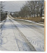 A Snow-covered Road Passes Wood Print by Joel Sartore