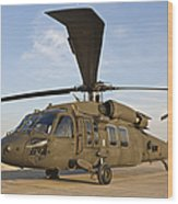 A Uh-60 Black Hawk Parked At A Military Wood Print