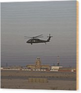 A Uh-60 Blackhawk Helicopter Flies Wood Print