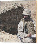 A U.s. Marine Communicates With Close Wood Print