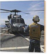 Airman Signals To An Mh-60s Sea Hawk Wood Print