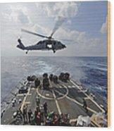 An Mh-60r Sea Hawk Transfers Supplies Wood Print