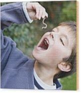 Boy Pretending To Eat An Earthworm Wood Print