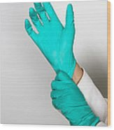 Doctor Putting On Gloves Wood Print