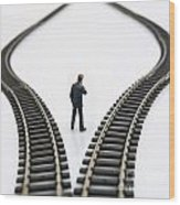 Figurine Between Two Tracks Leading Into Different Directions  Symbolic Image For Making Decisions Wood Print by Bernard Jaubert