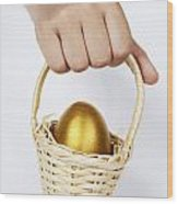 Girl's Hand Holding Basket With Golden Egg Wood Print