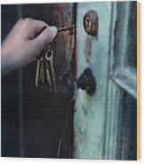 Hand Putting Vintage Key Into Lock Wood Print