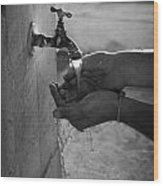 Hispanic Man Cupping Water And Washing Hands At Outdoor Tap Wood Print by Joe Fox