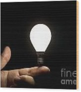 Lit Light Bulb Balancing On Finger Wood Print