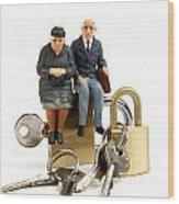 Miniature Figurines Of Elderly Couple Sitting On Padlocks Wood Print