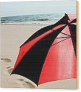 Red And Black Umbrella On The Beach With Footprints Wood Print