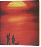 Silhouette Of Couple With Dog, Man Aiming, Sunset Wood Print by David De Lossy