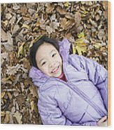 Smiling Girl Lying On Autumn Leaves Wood Print