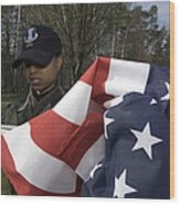 Soldier Unfurls A New Flag For Posting Wood Print by Stocktrek Images
