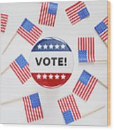 Studio Shot Of Vote Pin And Small American Flags Wood Print